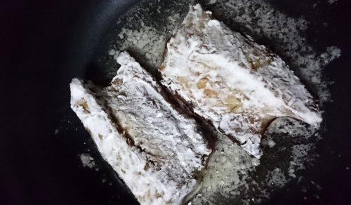 焼き鯖に片栗粉をつけて焼いている写真