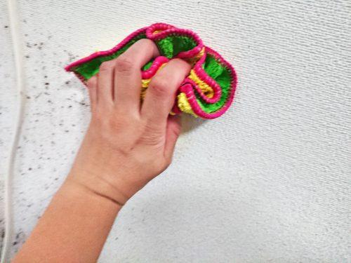 マイクロファイバー雑巾で壁紙を水拭きする写真